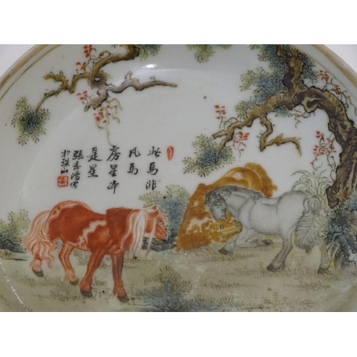 38 - A small Chinese famille rose dish, decorated with three horses in a landscape with gilt highlights. ...