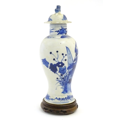 57 - A Chinese blue and white vase and cover with floral, foliate and bird detail. The lid with foo dog f...