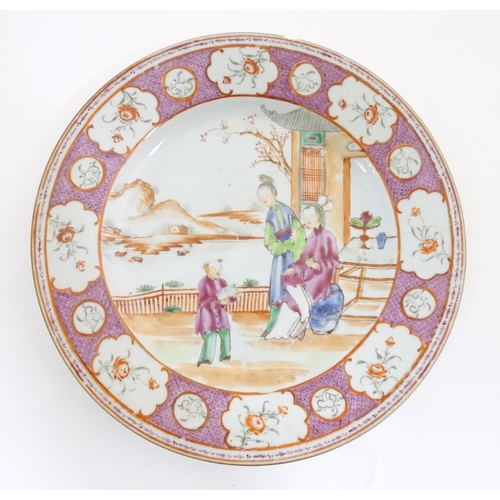17 - A Chinese famille rose plate depicting figures on a garden terrace with a mountainous landscape beyo...