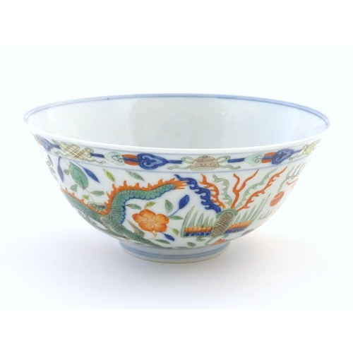 18 - A Chinese bowl with dragon and flaming pearl detail, with flowers, foliate and stylised clouds. Char...