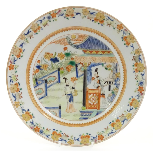 19 - A Chinese plate depicting two ladies in a garden terrace with flowers, foliate, vases, etc. Approx. ...