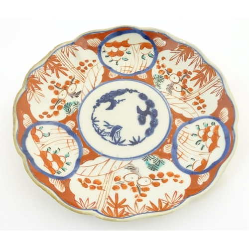 2 - Two Oriental plates, one decorated with panelled detail depicting landscape scenes. The other decora...