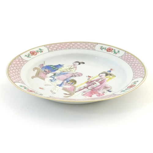 23 - A Chinese famille rose plate decorated with an interior scene with an elderly scholar on a day bed w...