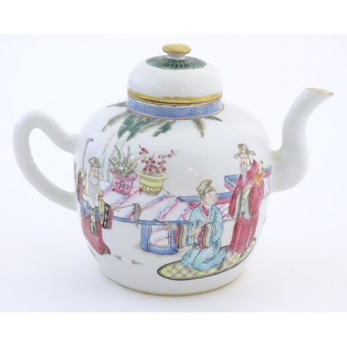 27 - A Chinese famille rose teapot depicting scholars with attendants on a terrace with a mountainous lan...