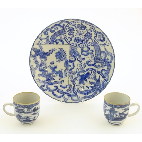 32 - An Oriental blue and white plate decorated with figures and scrolling flowers and foliage. With blue...