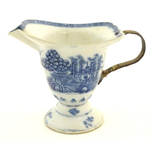 42 - An Oriental blue and white helmet jug decorated with a stylised landscape scene with pagodas, blosso...