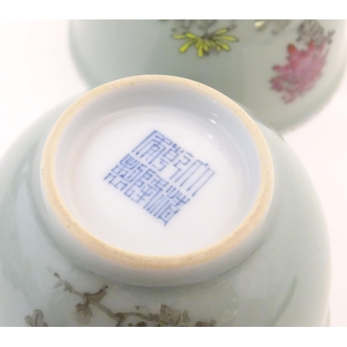 45 - A pair of Chinese tea bowls decorated with flowers and Oriental script. Character marks under. Appro...