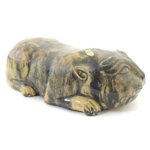 47 - An Oriental model of a recumbent animal, possibly a cat. Marked under. Approx. 9