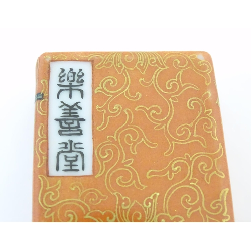 48 - A Chinese porcelain model of a book with scrolling gilt foliate detail and character marks. Approx. ...