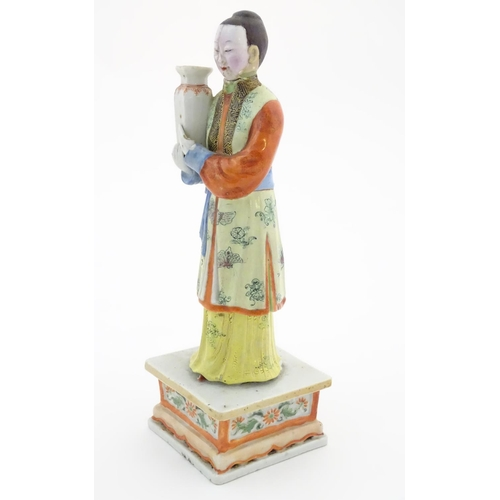 56 - An Oriental porcelain model of a male figure wearing a kimono with butterfly and floral detail holdi...