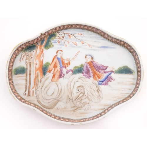 20 - A Chinese export dish of quatrefoil form depicting a landscape scene with a man playing a horn seate...