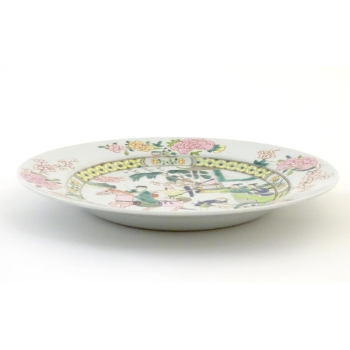21 - A Chinese famille rose plate depicting a landscape scene with a figure on horse back with an attenda...