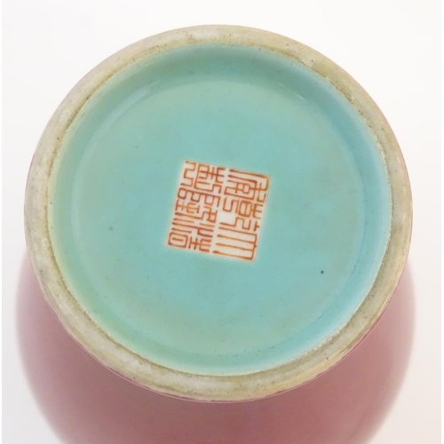 11 - A Chinese baluster vase with a bulbous rim, with a ruby pink glaze and a turquoise interior. Charact...