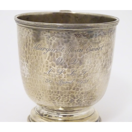 375 - A silver christening mug with hammered decoration. Hallmarked London 1931 maker Wakely and Wheeler 3...