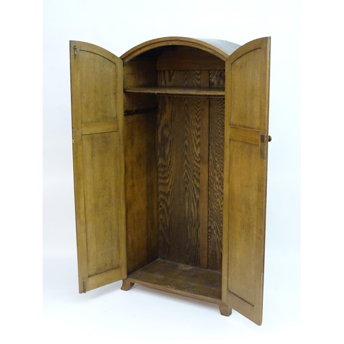 1518 - An early 20thC limed oak oak Heals wardrobe with a domed top above two panelled doors with turned wo...