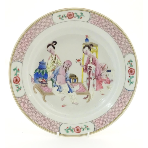 3 - A Chinese famille rose plate decorated with an interior scene with an elderly scholar on a day bed w...