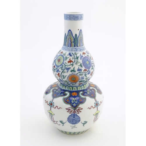 12 - A Chinese double gourd vase with doucai style decoration with scrolling floral and foliate detail. C...