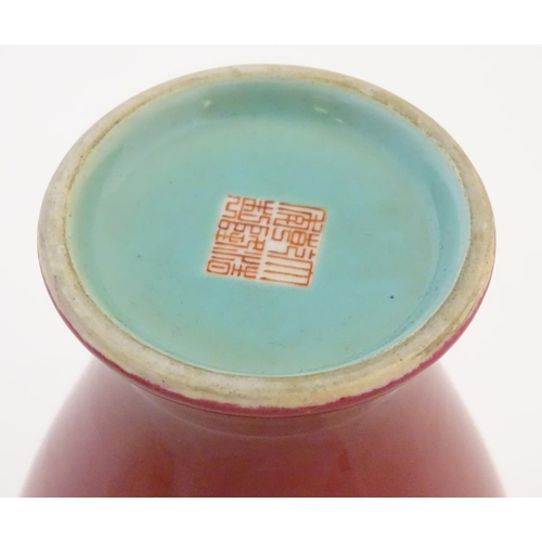 16 - A Chinese baluster vase with a bulbous rim, with a ruby pink glaze and a turquoise interior. Charact...