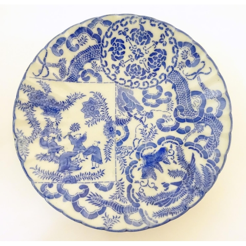 19 - An Oriental blue and white plate decorated with figures and scrolling flowers and foliage. With blue...