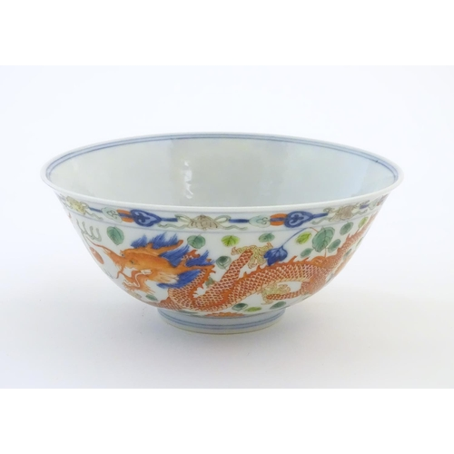 24 - A Chinese bowl with dragon and flaming pearl detail, with flowers, foliate and stylised clouds. Char...