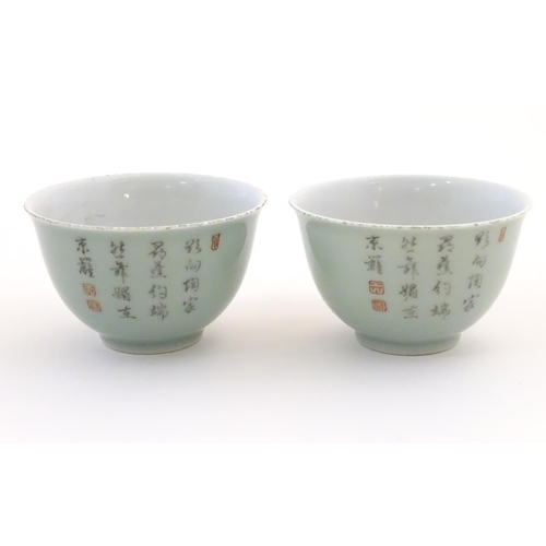 39 - A pair of Chinese tea bowls decorated with flowers and Oriental script. Character marks under. Appro...