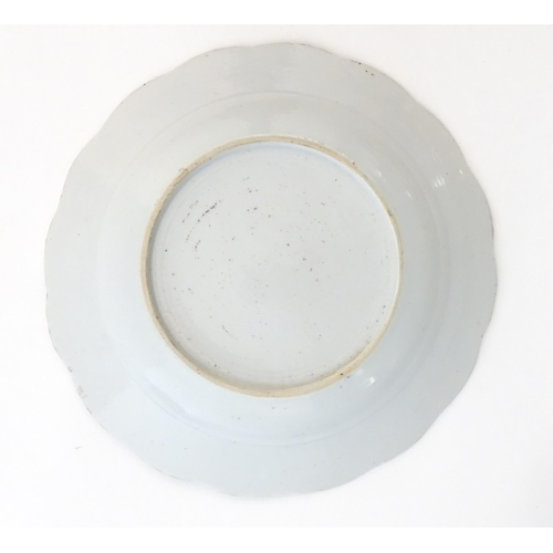 10A - A Chinese blue and white plate with a lobed rim decorated with a landscape scene with trees and flow...