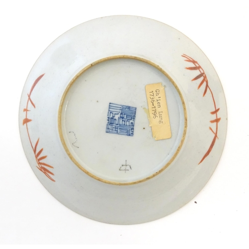 16A - A Chinese plate decorated with a landscape scene with a boat on a river. With red foliate motifs to ...