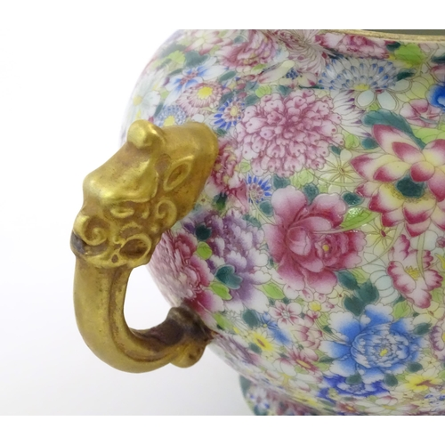 17 - A Chinese pot and cover with twin handles of stylised animal form, the body with mille fleur style f...