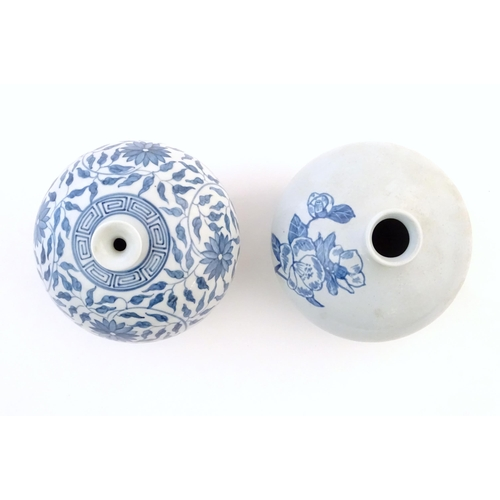 2 - An Oriental blue and white vase of globular form decorated with flowers and foliage. Character marks...
