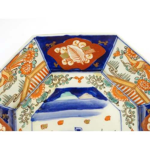 27 - A Japanese octagonal plate in the Imari palette decorated with birds, flowers and foliage, with cent...