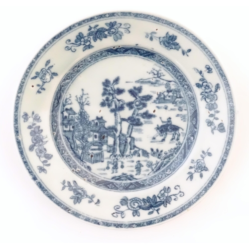 28 - A Chinese blue and white plate depicting a landscape scene with figures, trees, pagodas etc. with a ...