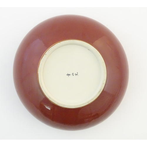 37 - A Japanese bowl with a red glaze and gilt rim. Character marks under. Approx. 4