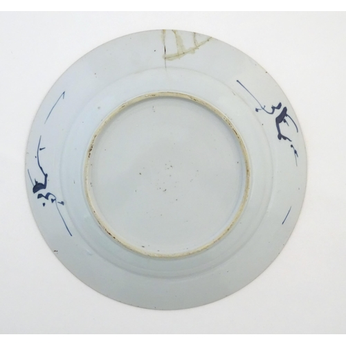 46 - A Chinese blue and white plate decorated with flowers and foliage. With stylised motifs to reverse. ...