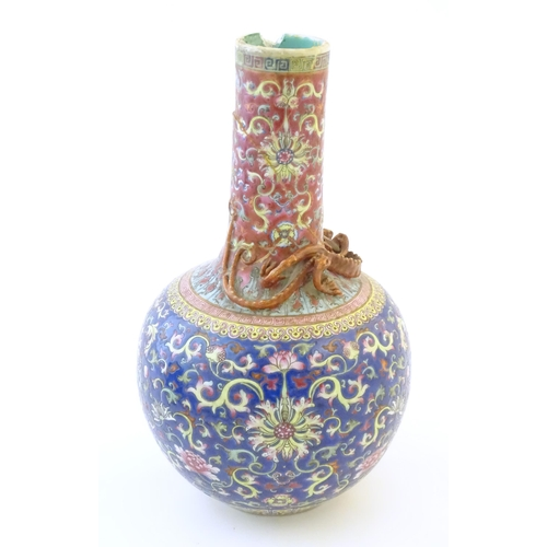 8 - A Chinese bottle vase with scrolling floral and foliate detail, and applied dragon decoration to nec...