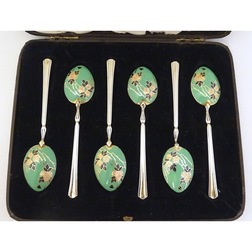 602 - A cased set of six silver teaspoons with gilt and enamel floral and foliate decoration to bowl, hall...