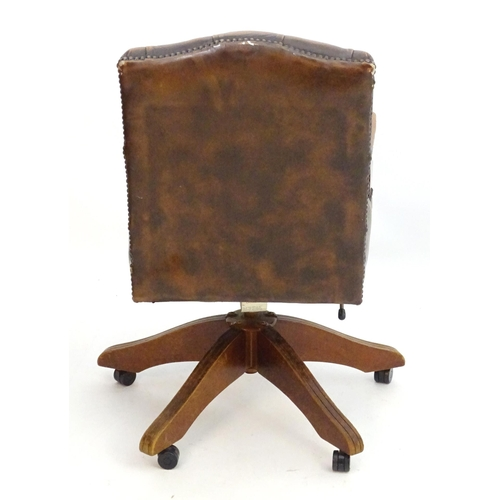 2043 - A late 20thC desk chair with deep buttoned leather upholstery and shaped arms above a five spoke bas...