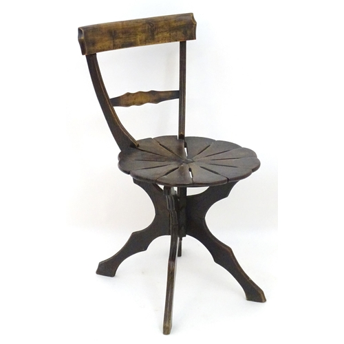 2044 - An early 20thC oak and beech chair with a shaped top and mid rail united by tapering supports, havin...