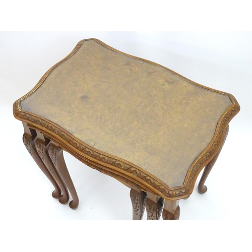 2045 - A nest of mid 20thC walnut tables, having three graduated tables with shaped and carved legs. 23 1/2...