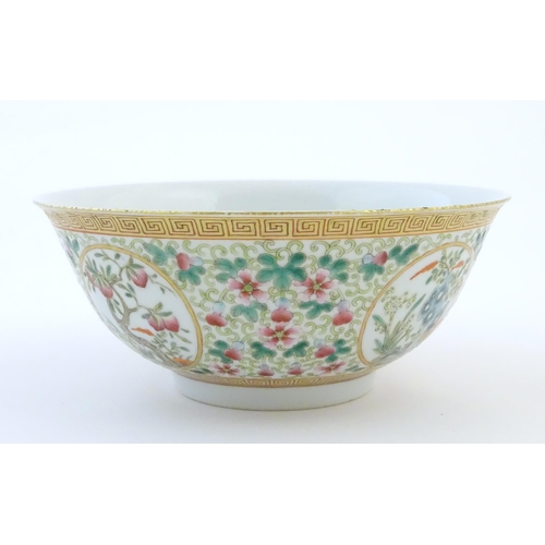 1 - A Chinese famille verte bowl decorated with fruiting trees and landscapes scenes in roundels and scr...