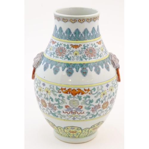 10 - A Chinese famille verte vase with a bulbous body with twin ring mask handles, decorated with scrolli...
