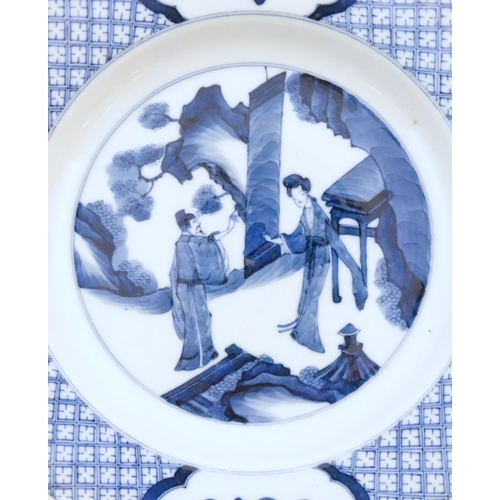 24A - A Chinese blue and white plate decorated with two figures in a landscape scene, the border with ausp...