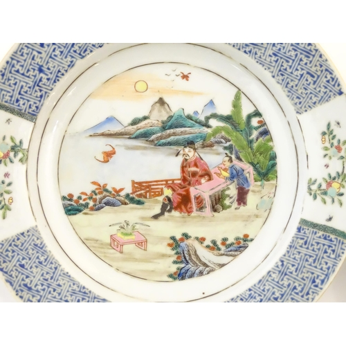 31A - A pair of Chinese plates depicting a two figures in a garden watching a bat, with sea and mountains ...