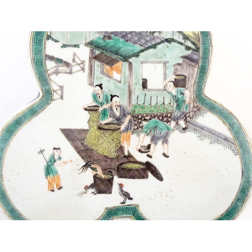 44 - A Chinese famille verte stand of trefoil form depicting figures sifting grain and shooing chickens. ...