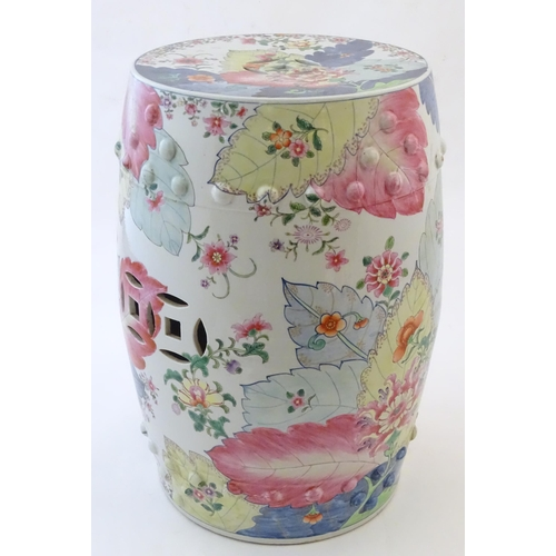 32 - A Chinese famille rose garden seat of barrel form with pierced roundels, decorated with flowers and ...