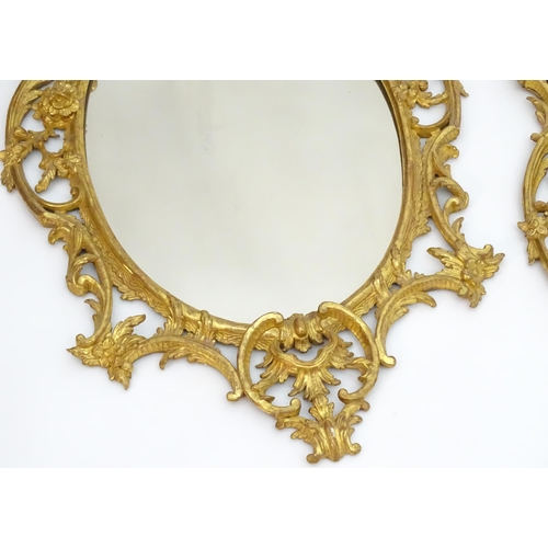 2015 - A pair of late 19thC / early 20thC gilt mirrors with gilt and gesso frames and oval mirrored glass c...