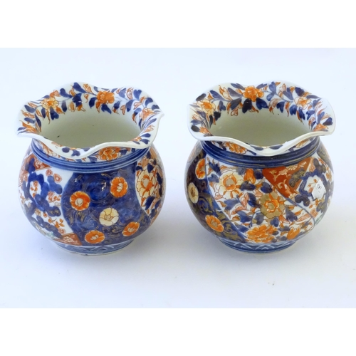 47 - Two Oriental vases of bulbous form with flared rims decorated in the Imari palette with flowers and ...