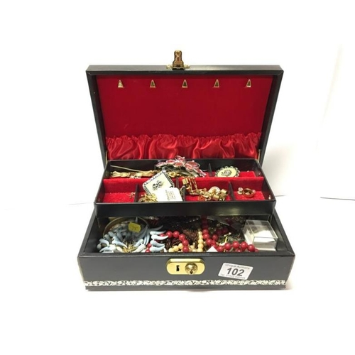 102 - A jewellery box and contents including necklaces, brooches etc...