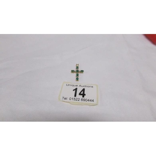 14 - An emerald and diamond yellow gold cross...
