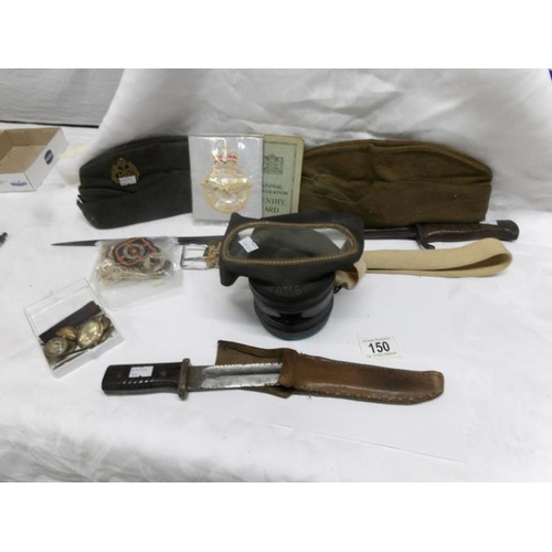 150 - A bayonet, one other knife, army & RAF caps with badges, a gas mask with box and other small accesso...