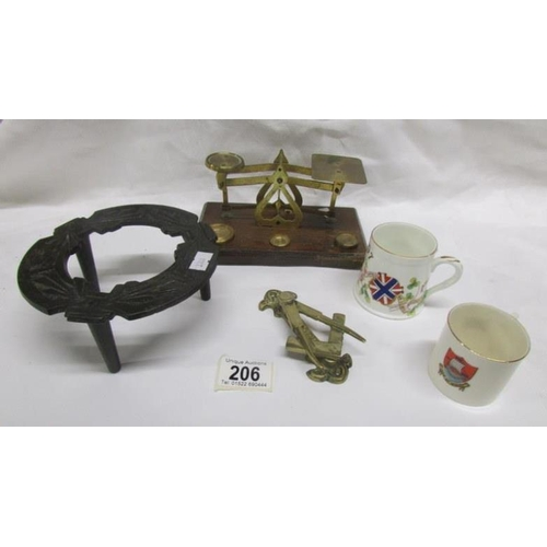 206 - A brass postal scale, a cast iron trivet, a brass Masonic themed door knocker and 2 commemorative cu...